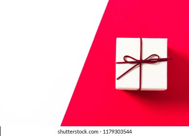 White gift box on red and white background. Top view. Copyspace