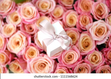 White gift box with pink ribbon on floral background. Minimal concept.