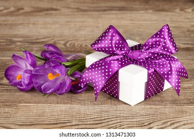 White gift box with a purple bow and a bouquet of crocuses