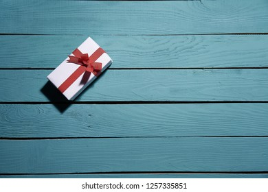 White gift box with a red bow on blue wooden planks, hard light