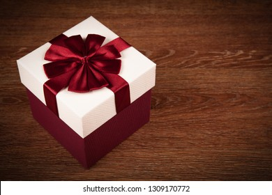 white gift box with red bow on a wooden background close up