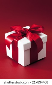 White gift box with red bow against red background