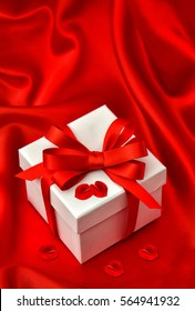White gift box with red bow ribbon and roses flower petals over smooth satin background