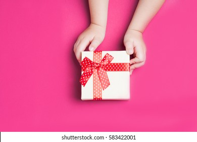 White gift box with red bow in the children's hands on pink background