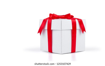 White gift box with red ribbon bow isolated on white background.