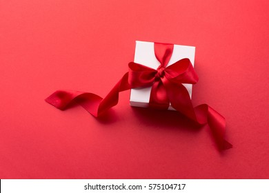 White Gift box with red ribbon on red background. Holiday Birthday Valentines day concept. Top view