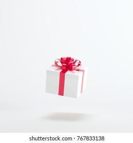 White gift box with red ribbon floating on white background. minimal christmas concept idea.