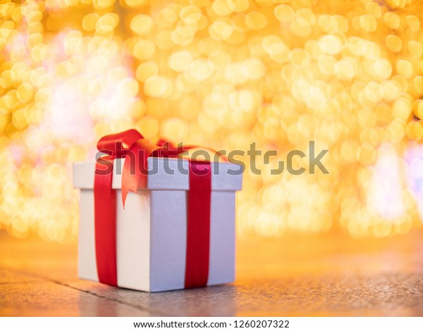 White gift box and red ribbon with yellow bokeh circle light background for celebration christmas day and new year party