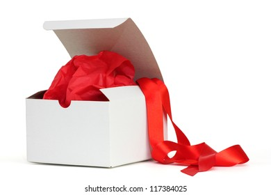 White gift box with red tissue and a red ribbon