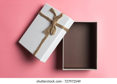 White gift box, ribbon bundle, cotton rope, placed on pink background.