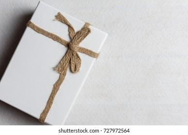 White gift box, ribbon bundle, cotton rope, placed on white background.