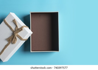 White gift box, ribbon bundle, cotton rope, placed on a blue background.