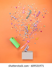 White gift box with various party confetti, streamers, noisemakers and decoration on a blue background. Colorful celebration concept.