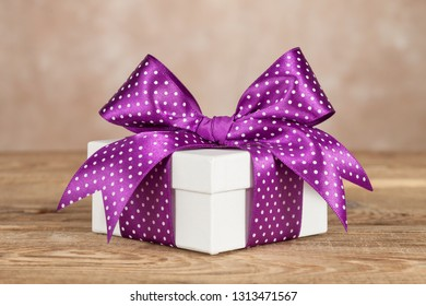 White gift box with a violet bow on the old board
