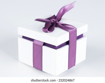 White gift box with violet ribbon bow, isolated on white background