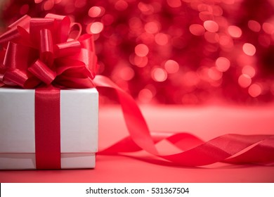 White gift box wrap with red ribbon bow over abstract blur festive light bokeh background with copy space