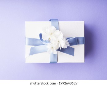White gift box wrapped with blue ribbon and decor flowers on purple background