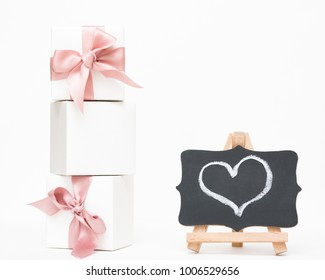 White gift boxes of the famous jewelry brand with bracelets and charms with a pink ribbon. Mock up. Empty place for an inscription. Postcard for the holiday. Heart drawn chalk on a blackboard.