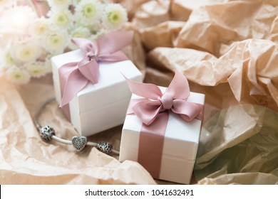 White gift boxes of the famous jewelry brand with charms bracelets with a pink ribbon. Mock up. Empty place for an inscription or text. Postcard for the holiday.