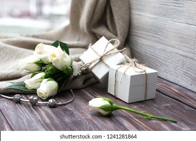 White gift boxes of a famous jewelry brand, a small bouquet of white roses and a silver bracelet with charms. Holiday concept. Wedding. Valentine's Day. Birthday.