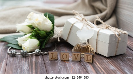 White gift boxes of a famous jewelry brand, a small bouquet of white roses and a silver bracelet with charms. Holiday concept. Wedding. Valentine's Day. Birthday.card.