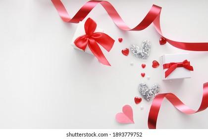 Weiße Geschenkbox, rote Herzen und Band auf weißem Hintergrund. Valentinstag-Komposition. Kopiert Platz. Das Konzept von Urlaub und Liebe.