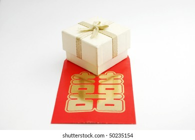 A white gift or jewelry box a Chinese double happiness red packet.
