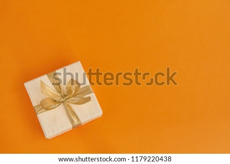 White Gift Or Present Box Decorated With Golden Ribbon On Orange Background Top View