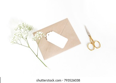 White gift tag with craft paper envelope, golden scissors and baby's breath Gypsophila flowers isolated on white table background. Wedding or birthday styled stock photo, top view, flat lay compositio