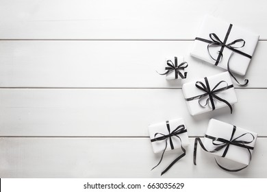 White gifts with black ribbon on white table. Mock up.