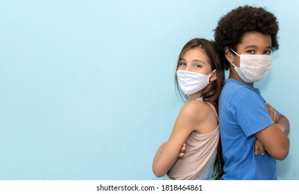 a white girl and an afro boy with his back to each other with protective mask against covid19 on yellow background