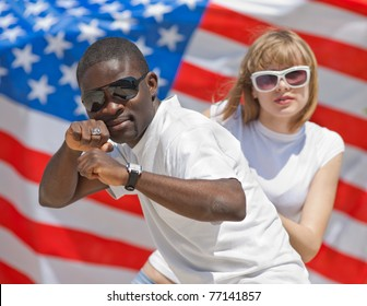 White girl and black guy dancing outdoors. White girl and black guy on background of American flag