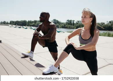 White girl and black man do stretching on the inner muscles of the thighs with his foot resting on a bench.
