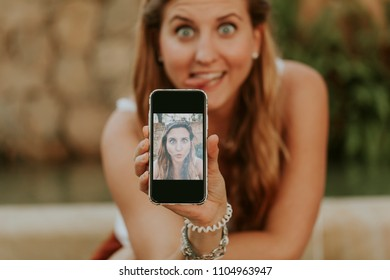 White girl holding a mobile phone and showing a selfie photo took by herself with funny expression.