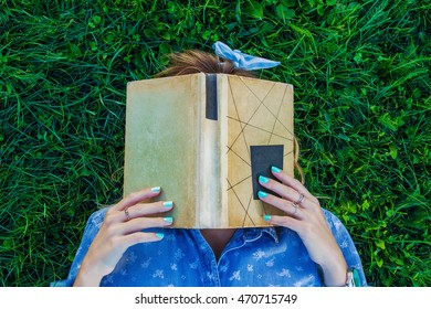 white girl with a manicure and a book lying on the grass / girl with book