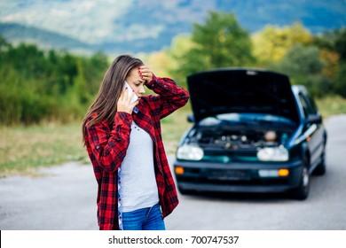 White girl model standing near the broken car calling for auto repair service
