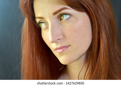 White girl with red hair and green eyes with eyelash extensions on a dark background looks seriously right with glow