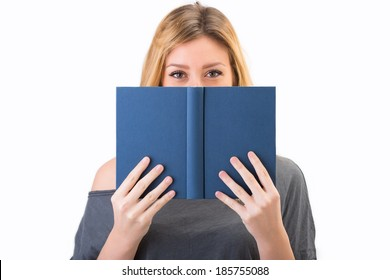 White girl smile and hides his face behind a book. Studio portrait of blonde model