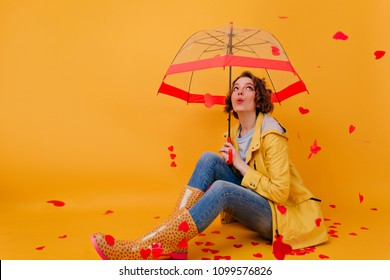 White girl with umbrella posing under heart rain. Studio shot of winsome young woman enjoying photoshoot in valentine's day.