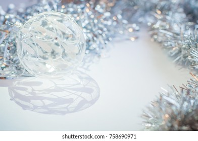 White glass ball on a white background with a beautiful shadow.  Silver tinsel. New Year and Christmas decoration.