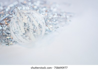 White glass ball on a white background.  Silver tinsel. New Year and Christmas decoration.