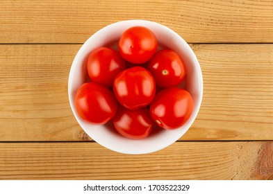 White glass bowl with red tomato cherry on wooden table. Top view