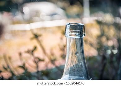 white glass carboy bottleneck on blurred background