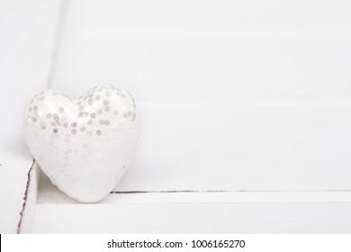white glitter heart on white background