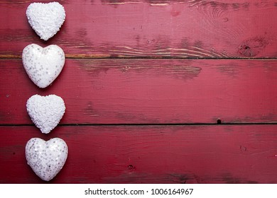 white glitter hearts on a red wooden background