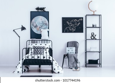 White globe on the shelf next to a chair with blanket and astronaut poster in kid's bedroom interior with bed
