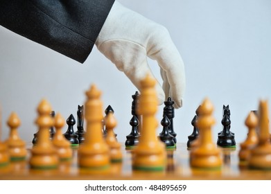 White glove moving a chess piece. Planning and decision theme