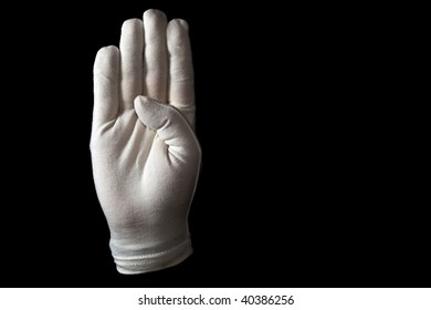 A white gloved hand isolated on black background. American sign language alphabet B.