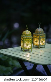 White glowing lanterns with delicate design on table in a garden