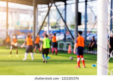 White goalposts and mesh of goal with blurry football players. football academy.